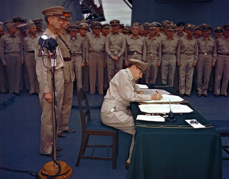 Gen. Douglas MacArthur signs the Japanese surrender documents Sept. 2, 1945, aboard the USS Missouri in Tokyo Bay. Lt. Gen. Jonathan Wainwright, left foreground, who surrendered Bataan to the Japanese, and British Lt. Gen. A. E. Percival, next to Wainwright, who surrendered Singapore, observe the ceremony marking the end of World War II. (AP Photo) Ref #: PA.4762828