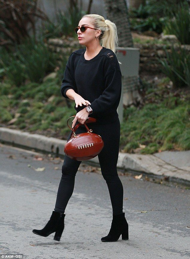 All star! Lady Gaga sported a funky football shaped handbag while visiting actor Bradley C...