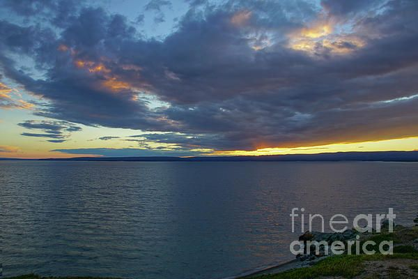 Yellowstone Lake located in the United States first national park, Yellowstone National Park, provides a beautiful view of the sunset as the clouds and steam from geysers combine to grab an array of color into the sky.