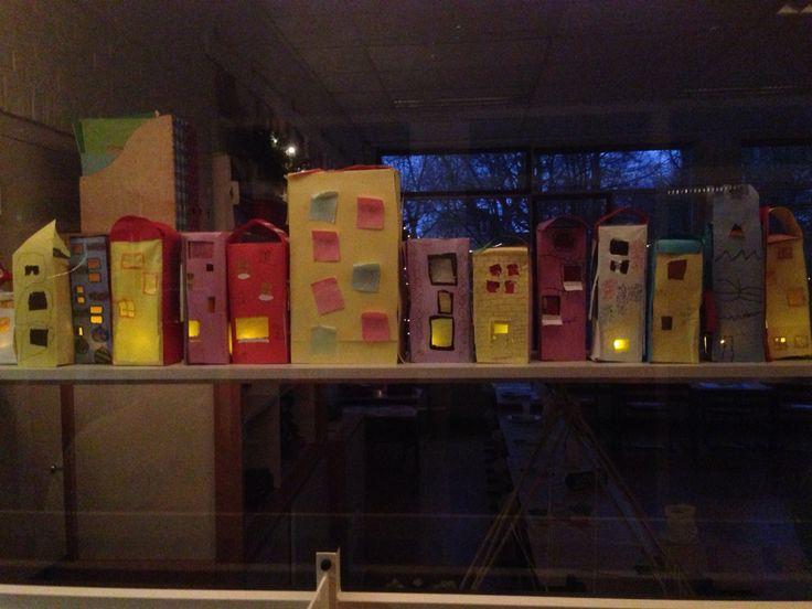 Straatje met huisjes in december. Met nep-waxinelichtje achter de ramen.