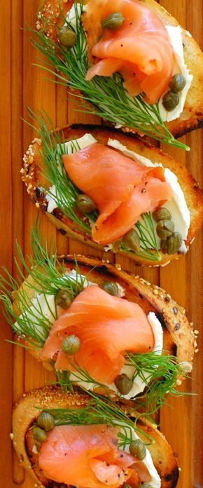 Smoked salmon dill and capers appetizer starts with a toasted baguette, coated with cream cheese, dill weed, capers and smoked salmon.
