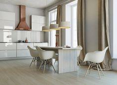 Bellissima cucina bianca minimal con elementi neutri naturali, tavolo in essenza legnosa di colore chiaro, morbidi drappeggi e la cappa in rame