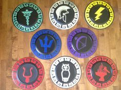 Percy Jackson-inspired shields. Hermes, Ares, Zeus, Poseidon, Artemis, Hades, Athena, and Hephaestus symbols with Greek borders. Made these with colored duct tape on 13 inch diameter plastic (melamine?)platters that only cost $1.50 each at a party supply store.