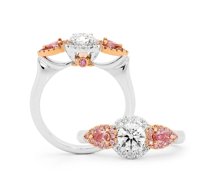 A handcrafted white gold, rose gold, pink and white diamond ring. Featuring a central round brilliant cut diamond set between two Argyle pink pink cut diamonds surrounded by a halo of white and pink diamonds. The underside of the setting is also detailed with a pair of round brilliant cut diamonds. enquiries@rohanjewellery.com