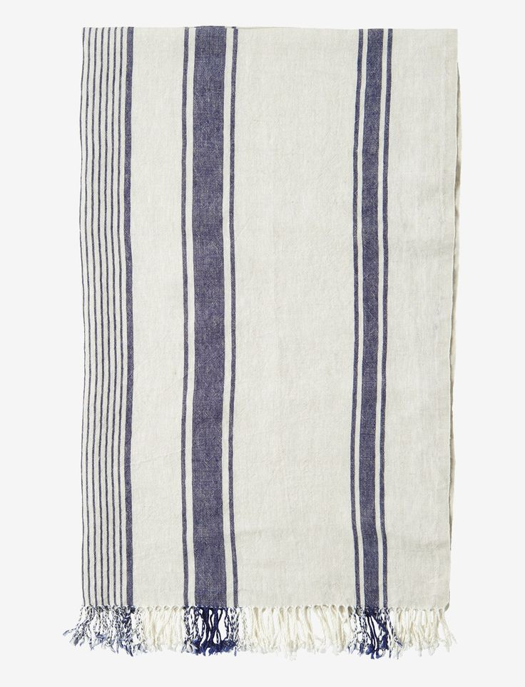 STRIPED LINEN BEACH TOWEL | Hardwearing, washed linen beach towel with a woven navy stripe. The linen is washed for suppleness and a textured, slightly worn in feel. Selvedge edges. Tassles at end. Made by a traditional, family run company in Lithuania.