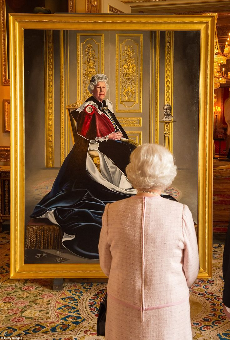 Queen Elizabeth II views a portrait of herself by British artist Henry Ward, marking six decades of patronage to the British Red Cross, which has been unveiled at Windsor Castle
