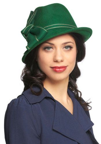 1930s-inspired fedora. This green topper, with contrasting cream stitching and adorned with an elegant trim ribbon