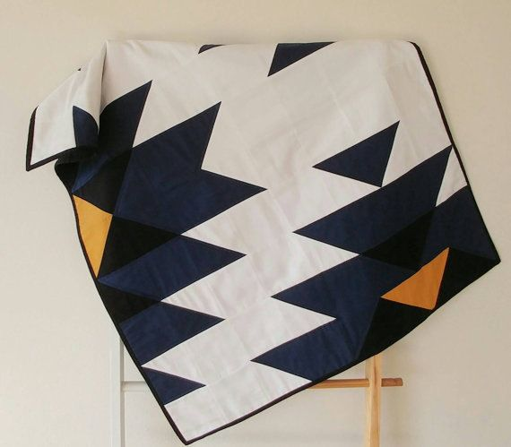 This modern quilt was inspired by native american indian art. It was made from 100% cotton fabric and lightweight cotton batting. The colors in this quilt are dark blue, black, yellow and white. The backing part is coal. There are two available sizes: Small: 34 x 42 inches/ 86 x 107 cm Large: 72 x 88 inches/ 182 x 224 cm The binding is hand stitched to the back in the traditional style.