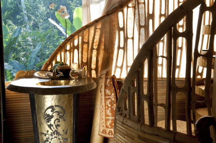 Master bathroom detail: The open-air bathroom with screen bamboo and paper wall, tropical forest beyond.  Brass sink and vanity hand made in a traditional Balinese 'prada' motif. Natrural-edge slice of stone as vanity counter top.  Traditional 'songket' textile from Threads of Life.    Sharma Springs, a private home designed for and belonging to Sumant and Myriam Sharma and their four daughters.  Located on the Ayung River valley, Sibang, Bali, Indonesia. Architecture by Ibuku. Custom…