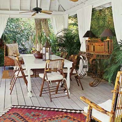"""Blending British Colonial–style furnishings (including a caned daybed bought for only $20 at a flea market) with laid-back, island-inspired touches like rattan lamps and flowing curtains creates an """"Out of Africa"""" ambiance in this outdoor entertaining space. 