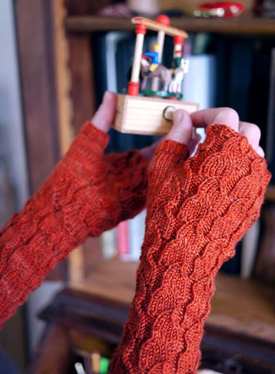 These cozy fingerless mitts in two sizes feature a fitted thumb gusset and deeply-textured openwork pattern