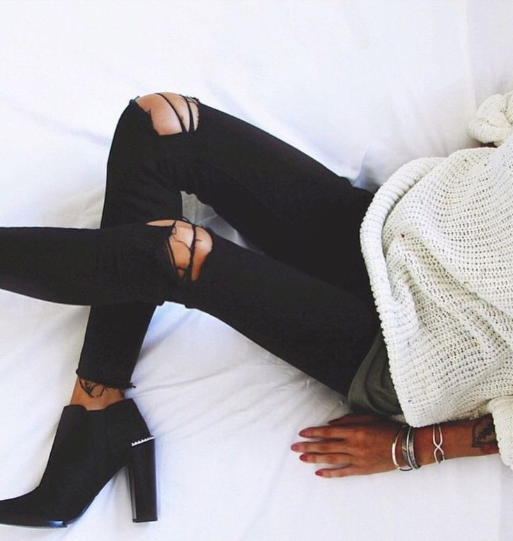 Cream over-sized sweater with ripped skinny jeans and black booties. Silver accessories.