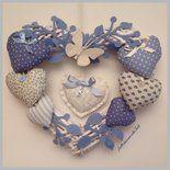 Cuore in vimini bianco decorato con rametti di feltro azzurri, una farfalla di feltro bianco, sei cuori imbottitti in cotonine americane fantasie varie sui toni dell'azzurro, ornati con fiocchi e b...