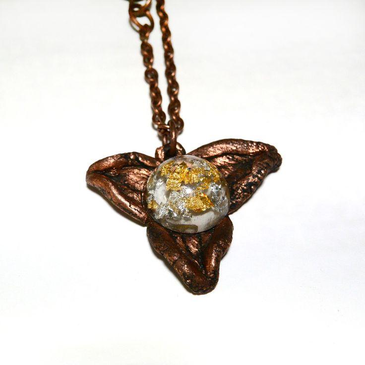 Кабошон из ювелирной эпоксидной смолы с золотой и серебрянной поталью, расположенной на разных уровнях, в центре трехлепескового медного цветка. Украшение необычное и эксклюзивное. Из-за размещения потали на разных уровнях создается ощущение большой глубины кабошона. Он красиво освещает медную основу всего кулона. Кулон на медной цепочке составленой из 2-х цепочек с разным звеном. Размер кулона примерно 5 см. 1500 руб.