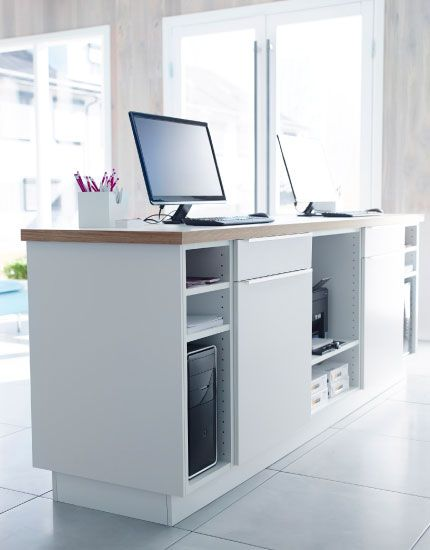 White kitchen cabinets with doors, drawers and worktop used as a front desk