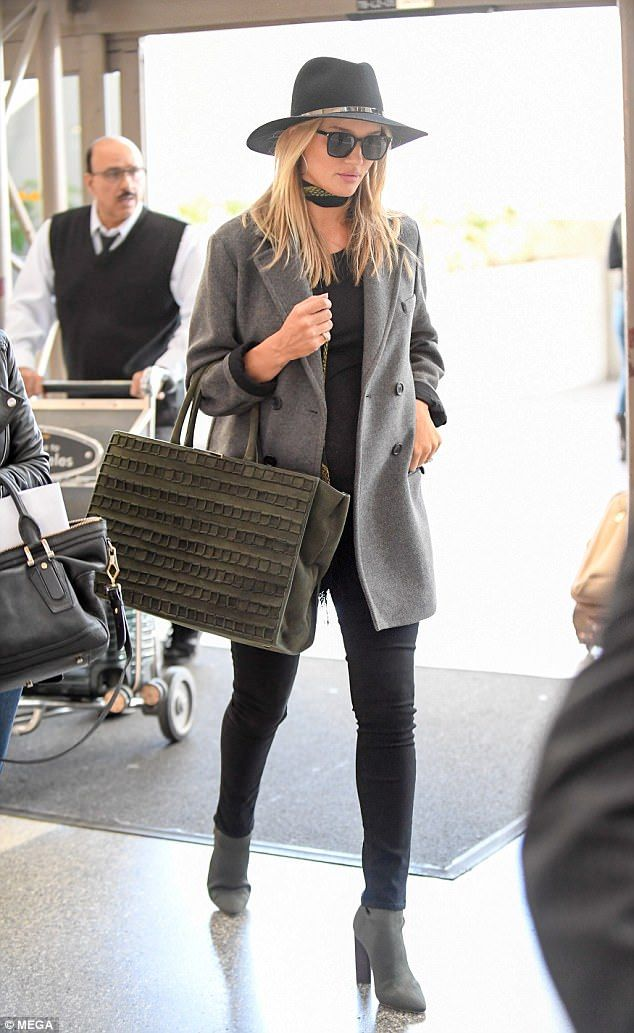 Jet-setter: Pregnant Rosie Huntington-Whiteley was seen arriving at Los Angeles International Airport on Tuesday