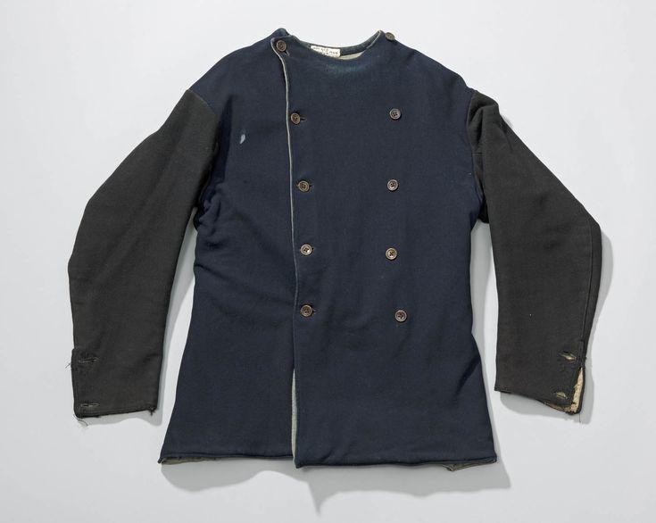 hemdrok van blauwe wol, Katwijk, man, voor 1948 hemdrok van blauwe wol, gevoerd met lichtblauwe geruwd katoen (flanel) en voorzien van benen knopen. De hemdrok heeft mouwen van een andere, donkerder wollen stof. Langs split en onderzijde mouwen een zwart kloskoordje. #ZuidHolland #Katwijk