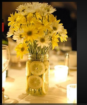 Centerpieces: yellow and white daisies with lemons in vase