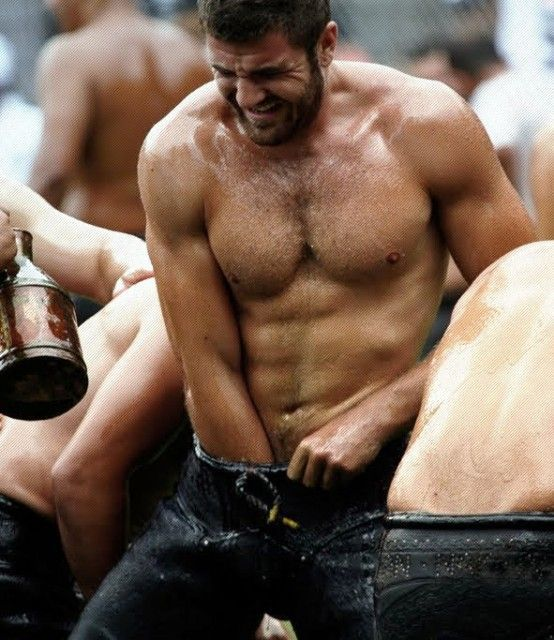 Men doused in oil battle it out