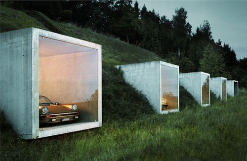 Built into a hillside, these concrete & glass cubes make up quite possibly the coolest garage.