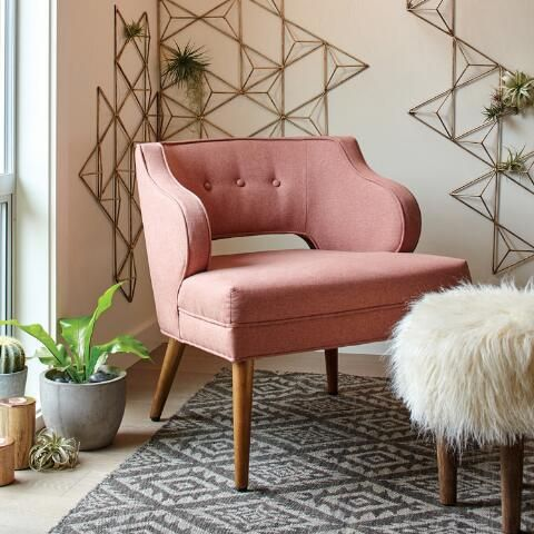 Boasting a body-hugging cutout silhouette, ultra-soft blush pink upholstery and conical birch-toned wood legs, our accent chair exudes a distinctly mid-century modern appeal.