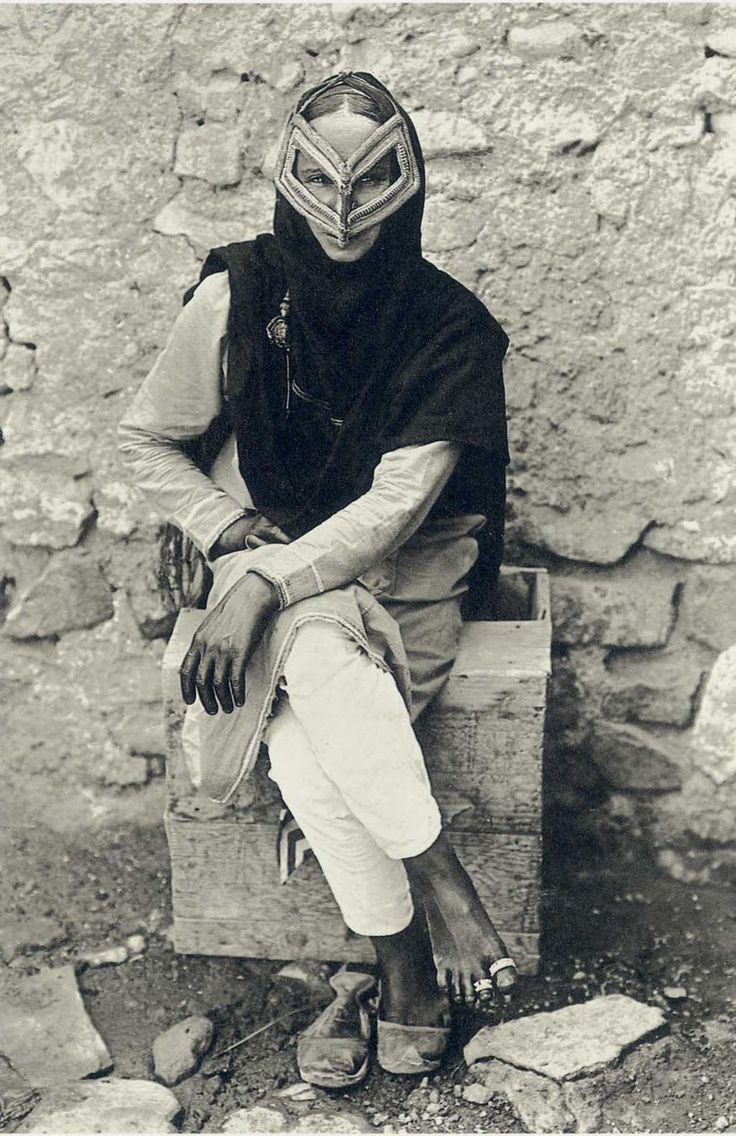 Portrait of an Arab woman wearing a traditional face mask in Muscat, Oman, 1905