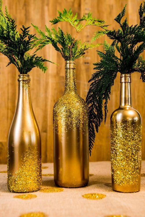 "There are many ways to dazzle your friends and family this holiday season. This is a very quick and very inexpensive way to add the elegance of  ""shimmer"" to your event. Materials: * Empty bottles (wine bottles work well) * Gold Spray paint * Gold Glitter * Spray glue Tools: * Plastic gloves * Plastic tarp * Paper plate Instructions: * Protect your hands from the spray by putting on gloves and lay the tarp to protect your surface. * Spray paint the entire bottle in gold, let dry."