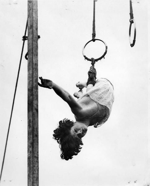"""Erma Ward, a circus trapeze artist, dangles by one hand from a ring high in a circus tent."""