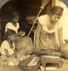 Tortilla making in El Salvador, 1900s. Mom's grinding the maize with a stone mano and metate as the elder daughter pats the dough into tortillas.
