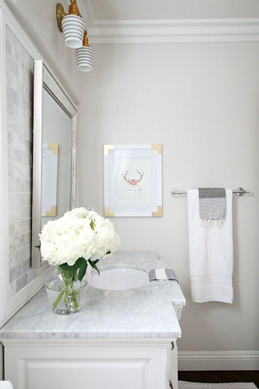 Children's Bathroom Reveal BM Pale Oak Sources: vanity (lowe's) | faucet (Newport Brass from The Bath Company) | flooring (lowe's) | cups & striped towels (west elm) | artwork (lucy) | owl soap dispenser & mirror (homegoods) | rug (target) | shower curtain (pottery barn) | light fixture & shades (schoolhouse electric co. ) | window treatment (custom) | marble tile backsplash (home depot) | paint color (pale oak benjamin moore)