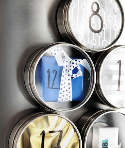Detail magnetickej nádoby z nehrdzavejúcej ocele upevnenej na chladničku, plnej malých zabalených darčekov.
