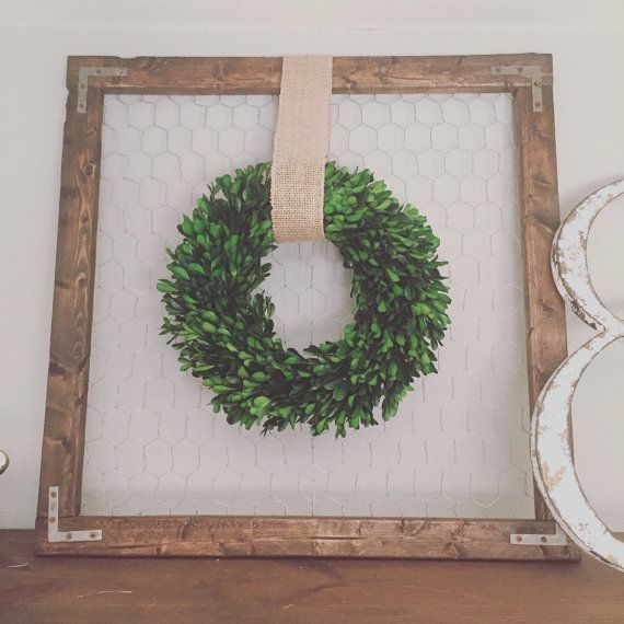 Farmhouse wood frame, chicken wire background with a 11 preserved boxwood wreath hung with a burlap ribbon. 20H x 20W x .50D