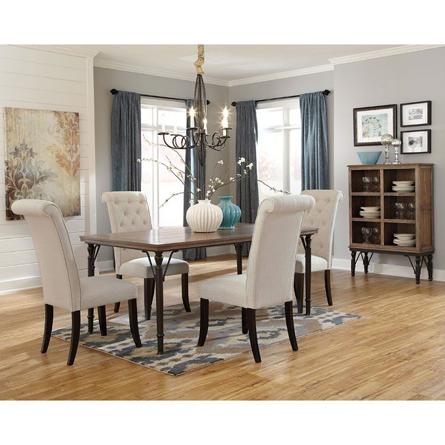 The Tripton Dining Room Set by Signature Design by Ashley Furniture flawlessly brings together a variety of materials to create an exciting contemporary designed collection perfect for any home. The rustic brown finished table top supported by the aged brown color of the tubular metal legs surrounded by the beautiful button tufted upholstered chairs.