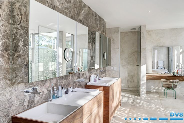 Modern Japanese home. Master en suite bathroom with timber and stone vanity, mirror units with magnifying lamp. Interplay of light and shadow from screening