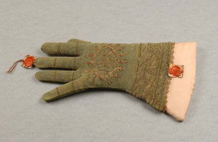 A single knitted silk glove, probably Italian, second half of 17th century, of pale green silk and gold threads, lined with matching plain silk fabric, with slightly angular gauntlet knitted with gold diagonal bands and medallions (similar to 23407), and IHS emblem within flame medallion, narrow gilt stripes to the fingers, 25 cm long, applied with two red wax seals which appear to be papal seals, possibly denoting that this glove may have been worn by a Pope.