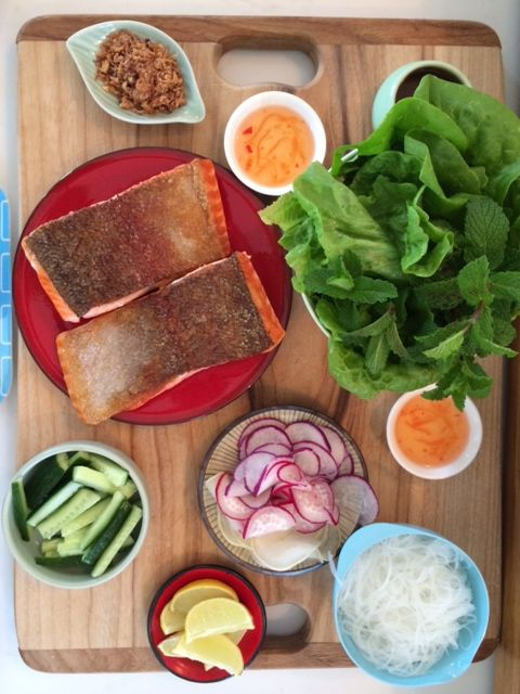 Crispy salmon in lettuce with rice noodles, salad, shallots and nuoc cham