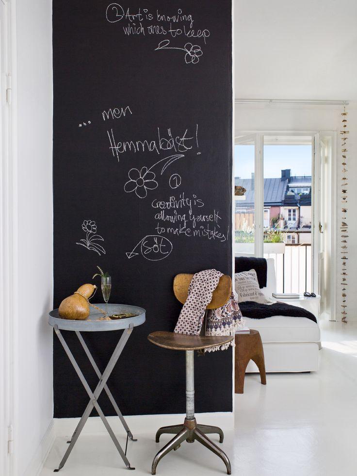Den svarta väggen i hallen är målad med griffelfärg. Zinkbord från Granit, stolen är ett containerfynd.