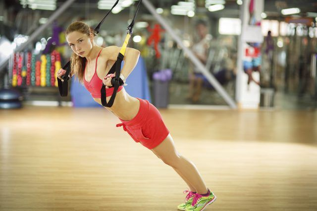 A young woman is strength training using TRX equipment.
