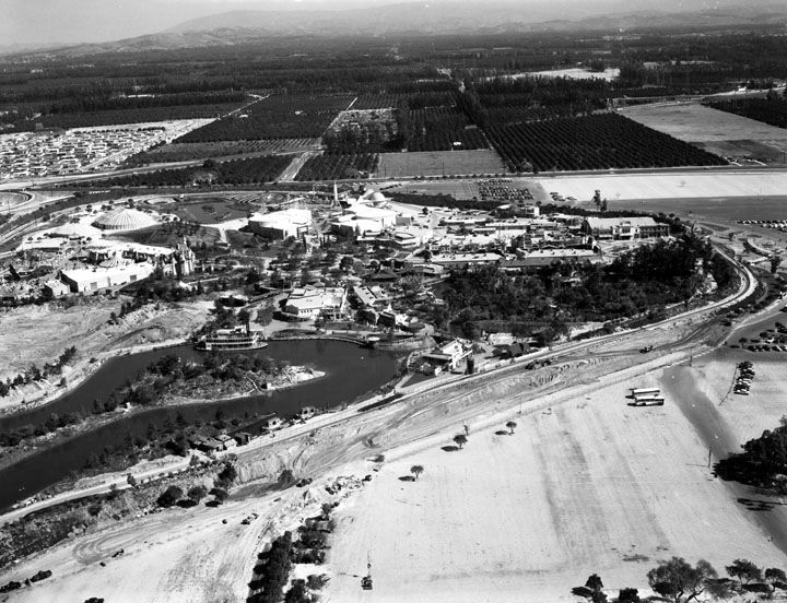 1956 Eastward Aerial view of Disneyland amusement park and surrounding neighborhoods in Anaheim. A large tent can be seen beyond Holiday Hill. | Water and Power Associates
