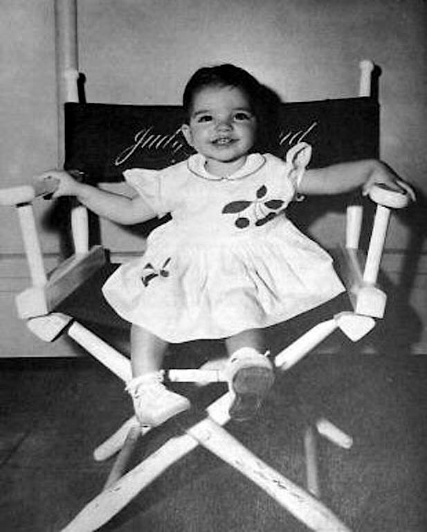 Liza Minnelli as a toddler sitting in her mother Judy Garland's chair.