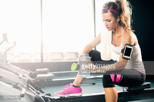 Stock Photo : Young woman holding water bottle in gym