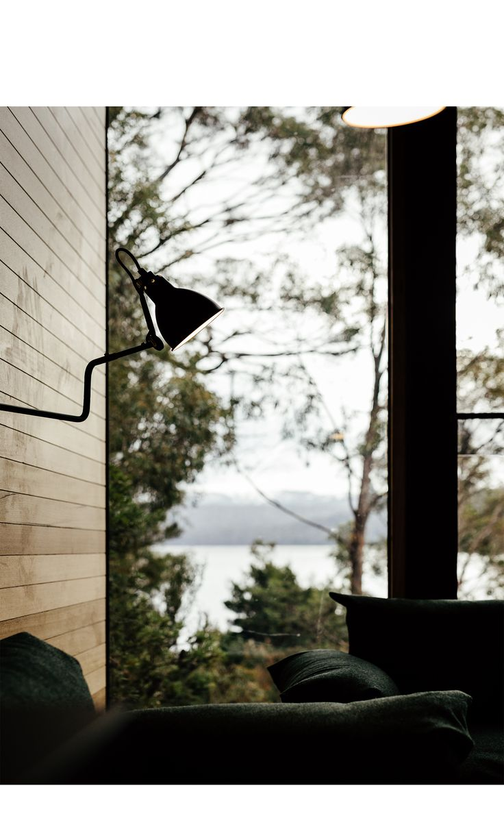 Guests discover the building through a narrow curved pathway leading from the Shorehouse, entering through the covered entry and climbing the stairs to a floating sun-filled room with picture windows overlooking Lake St Clair deep in Tasmanians World Heritage Area.