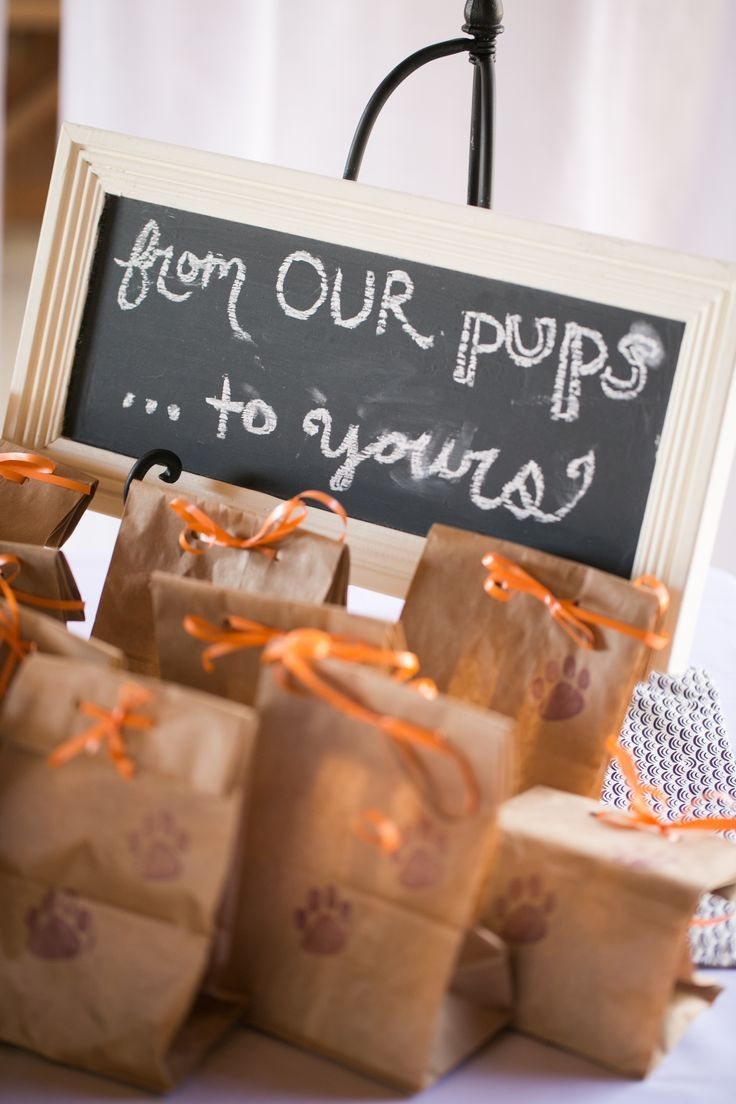 "For their guests' furry friends, Sarah and Brett filled brown bags with dog treats and presented them with a sign that says ""From our pups, to yours."""