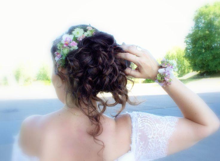 Bruid met polscorsage en haarversiering van echte bloemen in de kleuren wit, roze en groen.