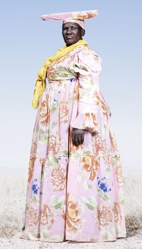 Herero woman in pink dress with yellow scarf: