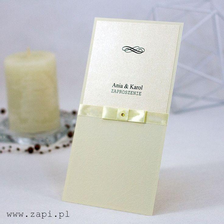 Eleganckie, kremowe zaproszenie ślubne wykonane na tłoczonym papierze dekoracyjnym z tasiemką satynową i złotą aplikacją.