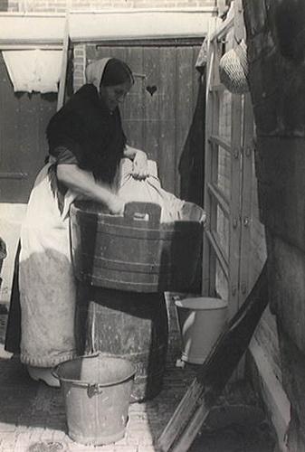 Scheveningse vrouw aan de was op een binnenplaatsje, zij gebruikt houten tobbe met wasplank, boender en wasstamper zij draagt nachtmutsje en zwarte omslagdoek 1930