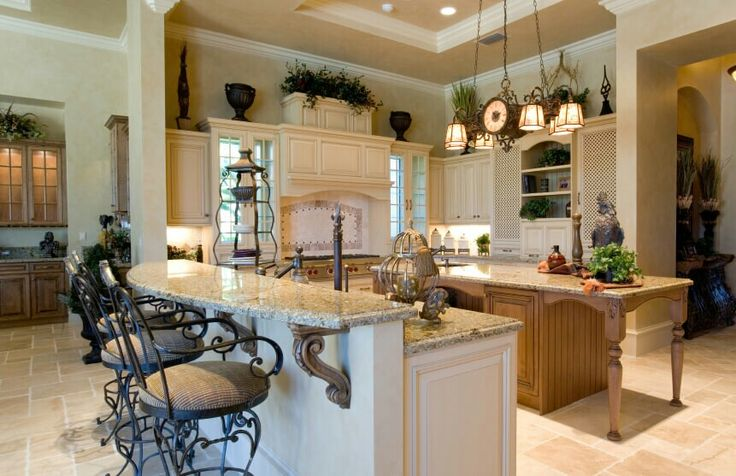 A French country kitchen with subtle, delicately carved accents on the island and eat-in bar. At the granite bar is a series of iron barstools with cushioned seats. A vintage iron clock light fixture hangs above the kitchen island. Above the cabinets,  #homestratosphere