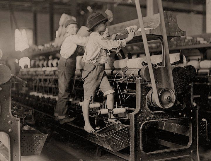 Child labor in the US - early 1900s. Some boys and girls were so small they had to climb up on to the spinning frame to mend broken threads and to put back the empty bobbins. Bibb Mill No. 1. Macon, Georgia.