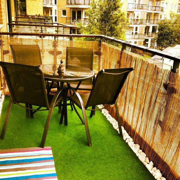brise-vue balcon en bambou, tapis d'aspect pelouse synthétique et déco en galets blancs